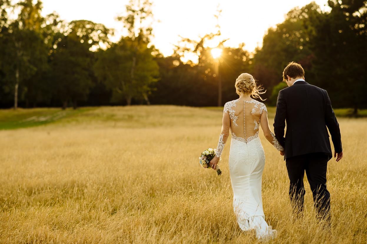 Pippingford Park wedding bride & groom walking in field